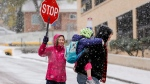 Crossing guard Angela Gieck, left, helps Will Gerbig, right, and his daughter, Madison Gerbig, 5, cross the street to kindergarten at Manitou Springs Elementary School as snow falls across the Pikes Peak region in Colorado Springs, Colo., Tuesday, Nov. 11, 2014. (The Colorado Springs Gazette, Michael Ciaglo)