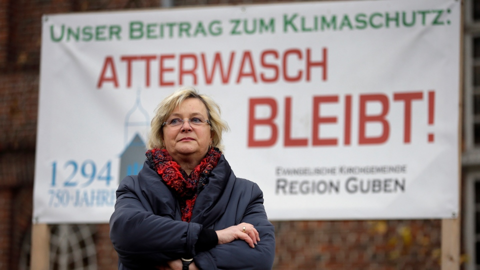 Monika Schulz-Hoepfner stands beside a protest poster against Vattenfall open-cast mining in the small village of Atterwasch, eastern Germany on Nov. 18, 2014. (AP / Michael Sohn)