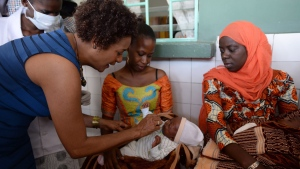 Former Governor General Michaelle Jean helps to administer a vaccine to fight rotavirus during an event at the Phillipe Maguilen Senghor's Health Centre in Dakar, Senegal on Nov. 28, 2014. (THE CANADIAN PRESS / Sean Kilpatrick)