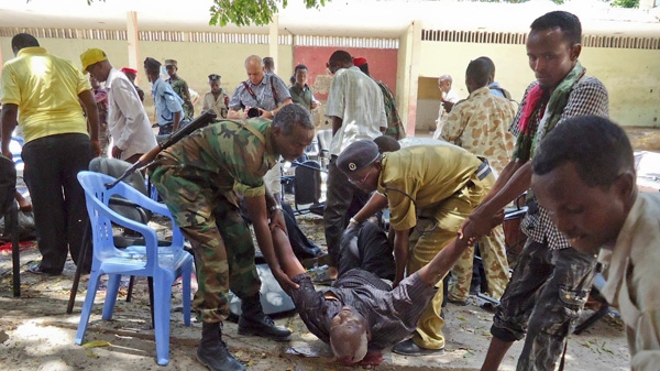 Somalis help a man wounded in a blast at the Somali National Theater in Mogadishu, Somalia Wednesday, April 4, 2012.(AP / Farah Abdi Warsameh)
