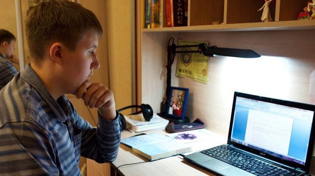 In this photo taken on Friday, Nov. 28, 2014, Denis Akimov, 15, sits in front of his laptop at home in Donetsk, eastern Ukraine. (AP Photo/Balint Szlanko)