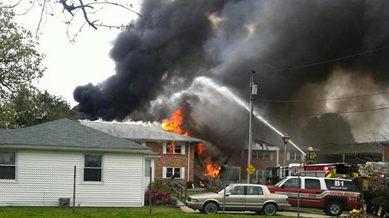 Smoke billows near an apartment complex where a Navy jet crashed in Virginia Beach, Va., Friday, April 6, 2012.  (AP / WVEC-TV)