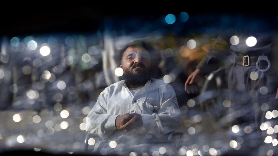 An Afghan man and security guard are seen through the shattered window of a damaged car at the site of a suicide attack in Kabul, Afghanistan, Thursday, Nov. 27, 2014. (AP / Rahmat Gul)