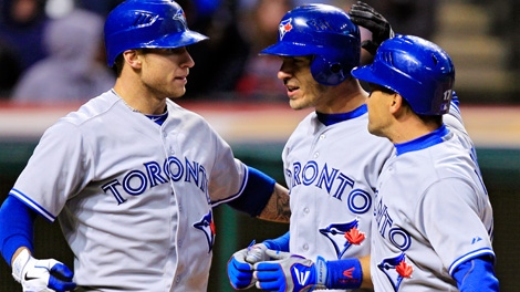 Toronto Blue Jays' J.P. Arencibia, center, celebrates with Brett Lawrie, left, and Omar Vizquel after Arencibia's three-run home run in the 16th inning of a baseball game against the Cleveland Indians, Thursday, April 5, 2012, in Cleveland. (AP Photo/Mark Duncan)