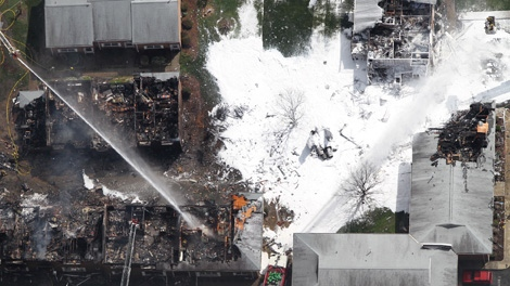 Emergency crews extinguish a fire at the scene of a jet crash Friday, April 6, 2012 in Virginia Beach, Va. (Ross Taylor / Virginian-Pilot)