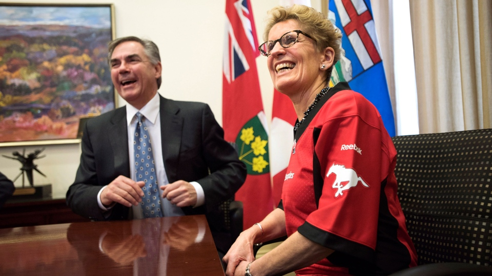Ontario Premier Kathleen Wynne, right, wears a Calgary Stampeders jersey while meeting with Alberta Premier Jim Prentice following a friendly bet on the Grey Cup at Queen's Park in Toronto on Wednesday, Dec. 3, 2014. (Darren Calabrese / THE CANADIAN PRESS)