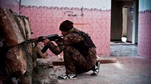 In this Nov. 1, 2014 photo, a Kurdish fighter battles the Islamic State in Kobani, Syria. (AP Photo/Jake Simkin)