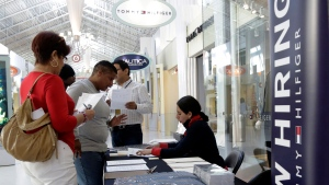 Tommy Hilfiger employee Sandra Hoyos talks with job applicants during a job fair at Dolphin Mall, in Miami on Oct. 28, 2014.  (AP / Lynne Sladky)