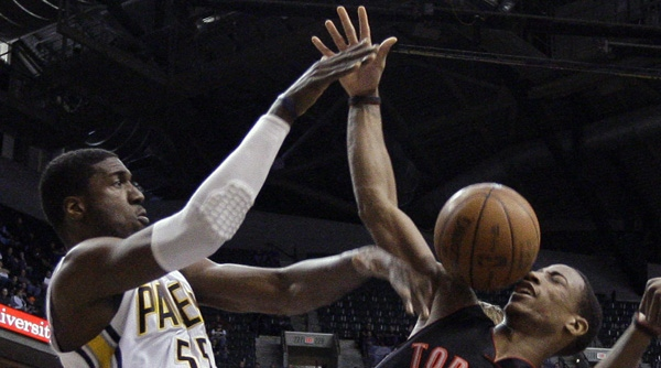 Indiana Pacers center Roy Hibbert, left, blocks the shot of Toronto Raptors guard DeMar DeRozan in the first half of an NBA basketball game in Indianapolis, Monday, April 9, 2012. (AP Photo/Michael Conroy)