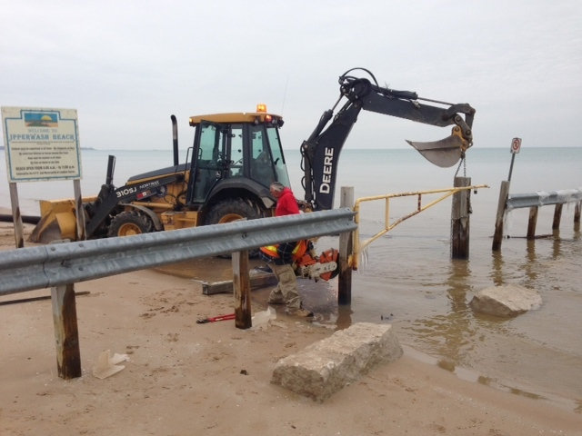 A crew works to remove a barrier for vehicles on Ipperwash Beach, east of Sarnia, Ont. on Friday, Dec. 5, 2014. (Bryan Bicknell / CTV London)