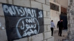 Two Jordanian men walk past graffiti depicting the flag of the Islamic State group in the city of Ma'an, Jordan, Oct. 28, 2014. (AP / Nasser Nasser)