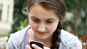 A girl plays with her phone in this undated image. (Denis Kuvaev / Shutterstock.com)