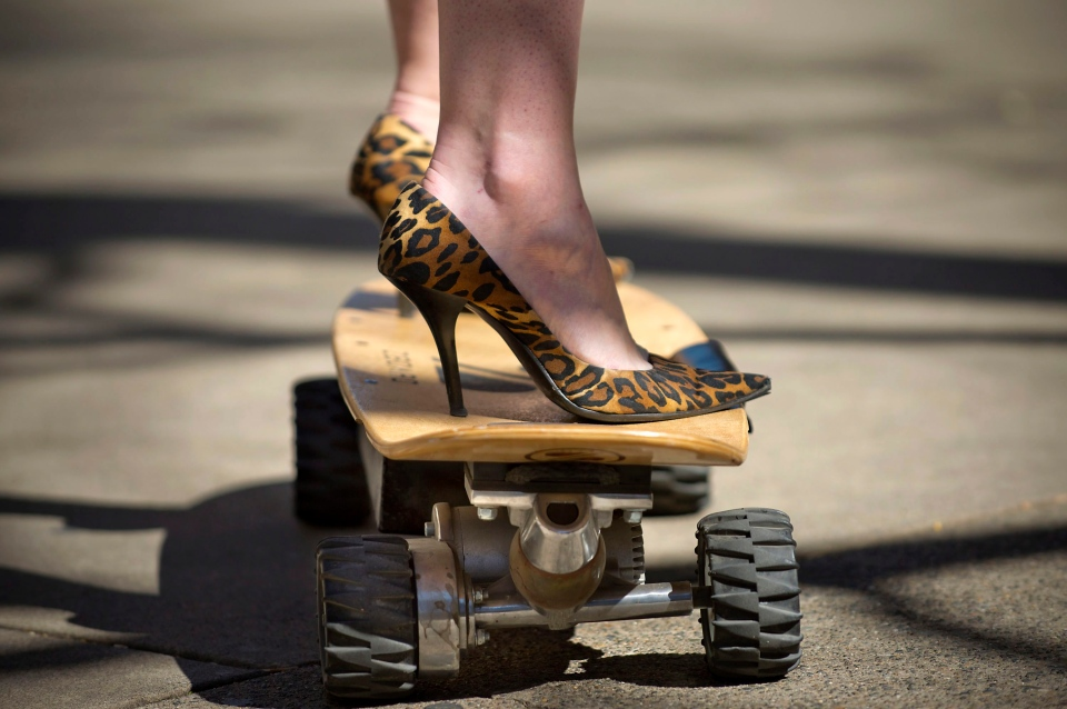 A woman wearing high heels tests the electrically powered skateboard called 'Zboard' near the State Capitol in Sacramento, Calif., Tuesday, March 11, 2014. (The Sacramento Bee / Randall Benton)