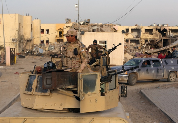 Iraqi security forces and Shiite fighters are deployed during a military operation to regain control of the University of Tikrit, 130 kilometres north of Baghdad, Iraq, Monday, Dec. 8, 2014. (AP / Hadi Mizban)