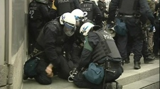 Montreal police arrest a tuition protester outside the National Bank head offices (April 11, 2012)