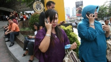 Indonesian women make phone calls as they are evacuated from a shopping mall after a strong earthquake was felt in Medan, Sumatra island, Indonesia, Wednesday, April 11, 2012. (AP / Binsar Bakkara)