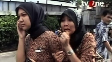 Two women react on a street shortly after they ran out from a building when a strong earthquake hit in Aceh in Indonesia, Wednesday, April 11, 2012. (TV One via AP Video)