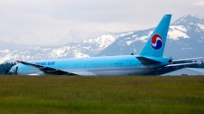 A Korean Air Boeing 777 is shown with a person near an open door on the runway at CFB Comox in Comox, B.C. on Tuesday, April 10, 2012. (Richard Warrington /  THE CANADIAN PRESS)