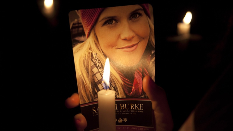 A lit candle lights up a picture of freestyle skier Sarah Burke during a memorial service for her in Whistler, B.C. Tuesday, April 10, 2012. Burke a freestyle skiing pioneer died Jan. 19, 2012 following an accident during a training session in Utah.