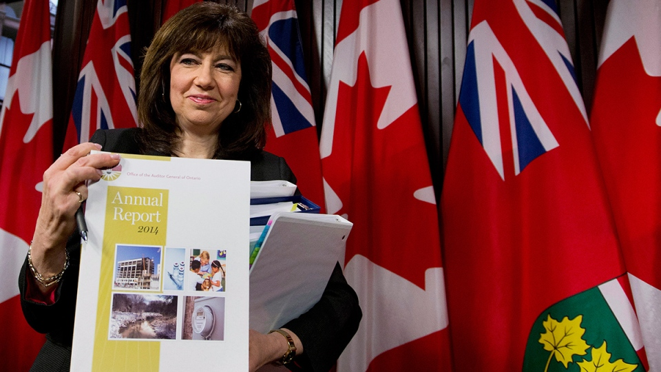 Auditor General Bonnie Lysyk holds a copy of her 2014 report at a news conference in Toronto on Tuesday, Dec. 9, 2014. (Nathan Denette / THE CANADIAN PRESS)