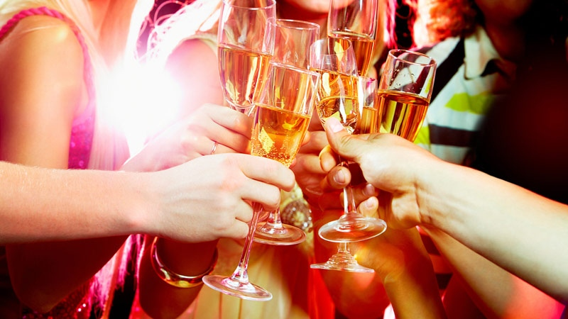 Holiday party goers drink sparkling wine