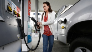 Lydia Holland replaces the gas nozzle after filling up at a gas station in Sacramento, Calif., Nov. 12, 2014. (AP / Rich Pedroncelli)