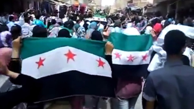 This image made from amateur video purports to show Syrians holding Syrian revolutionary flags during a demonstration in Deir el-Zour, Syria, on Thursday, April 12, 2012. (Ugarit News via AP video)