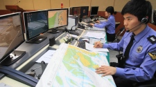 South Korean officials of the Incheon Maritime Police Agency monitor a situation room while on high alert in preparation for North Korea's planned launch of a Unha-3 rocket, in Incheon, South Korea, Thursday, April 12, 2012. (AP / Yonhap. Ha Sa-hun)