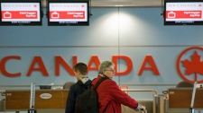 Passengers queue at an Air Canada check in desk at Trudeau Airport in Montreal, Friday, April 13, 2012. (Graham Hughes / THE CANADIAN PRESS)
