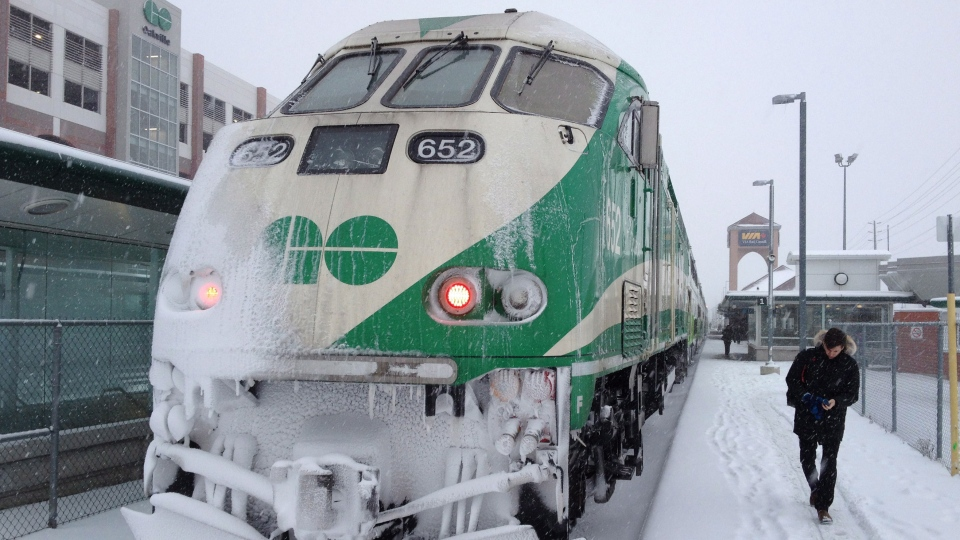 A commuter walks past a snow-covered Go Train in Oakville, Ont. on Thursday, Dec. 11, 2014. (Rich Buchan / THE CANADIAN PRESS)