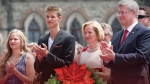 Prime Minister Stephen Harper is pictured with his wife Laureen Harper and their children Ben and Rachel during Canada Day celebrations on the cover of the prime minister's 2014 Christmas card. (THE CANADIAN PRESS)