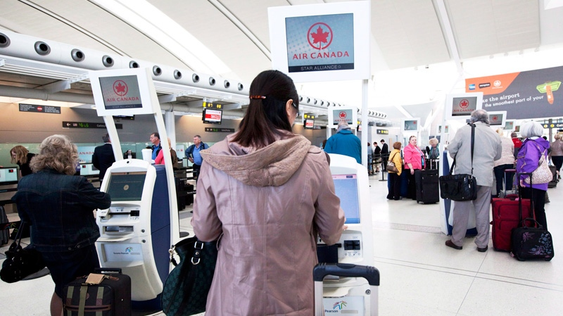 People check in at Pearson Airport in Toronto on Friday, April 13, 2012. (Michelle Siu / THE CANADIAN PRESS)