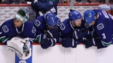 Vancouver Canucks goalie Roberto Luongo, left to right, Dan Hamhuis, Keith Ballard and Kevin Bieska sit on the bench in the final minute of third period of game two of first round NHL Stanley Cup playoff hockey action against the LA Kings at Rogers Arena in Vancouver, B.C. Friday, April, 13, 2012. The Kings went on to win the game 4-2 and lead the series 2-0. (THE CANADIAN PRESS/Jonathan Hayward)