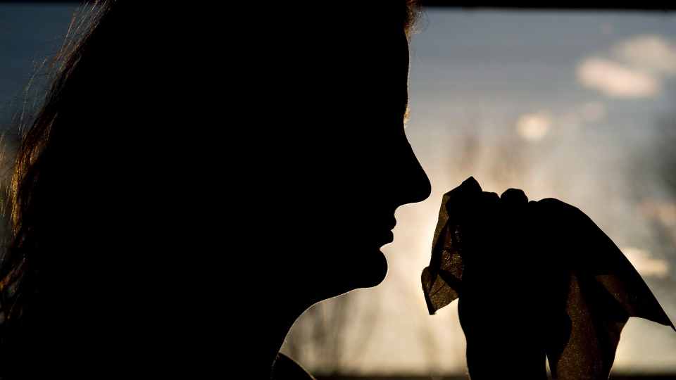 A woman is silhouetted as she uses a tissue to blow her nose in Toronto on Friday, November 21, 2014. (Nathan Denette / THE CANADIAN PRESS)