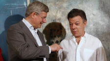 Canadian Prime Minister Stephen Harper, left, talks with Colombia's President Juan Manuel Santos during a signing ceremony in Cartagena, Colombia, Friday, April 13, 2012. Harper is in Cartagena to participate in the sixth Summit of the Americas. THE CANADIAN PRESS/Adrian Wyld