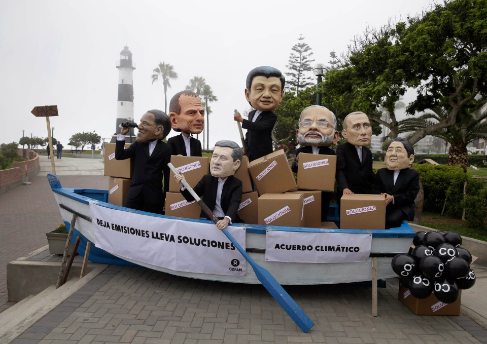 "Activists perform as heads of state, from left, President Barack Obama, Australia's Prime Minister Tony Abbott, Canada's Prime Minister Stephen Harper, China's President Xi Jinping, India's Narendra Modi, Russia's President Vladimir Putin and Japan's Prime Minister Shinzo Abe during the Climate Change Conference COP20 in Lima Peru, Friday, Dec. 12, 2014. The boat's sign reads in Spanish ""Leave behind emissions. Climatic agreement."" (AP Photo/Martin Mejia)"