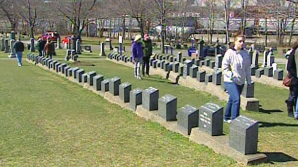 Tourists walk through the 150 graves belonging to Titanic victims in Halifax on Saturday, April 14, 2012.
