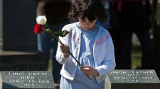 A child holds a flower that will be placed on a grave marker at a memorial service at Fairview Lawn Cemetery to mark the 100th anniversary of the sinking of RMS Titanic in Halifax on Sunday, April 15, 2012. (Andrew Vaughan / THE CANADIAN PRESS)