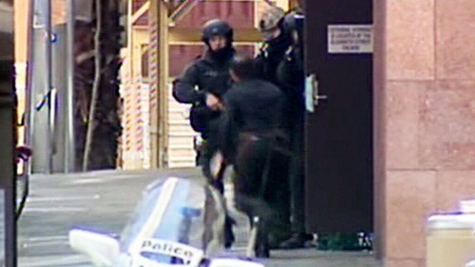 A hostage escapes from a Sydney, Australia cafe where a hostage situation is taking place on Monday, Dec. 15, 2014.