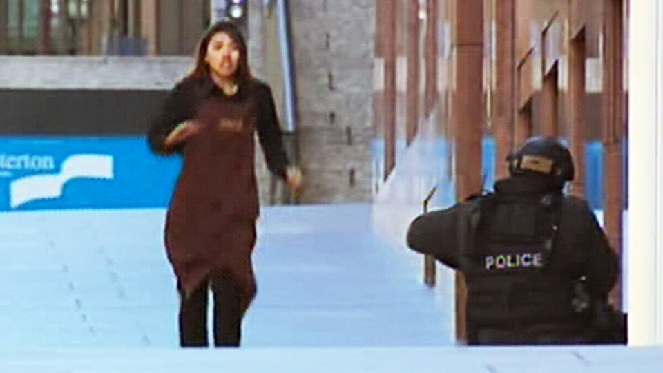 A woman held up in a hostage situation at a café in Sydney, Australia runs to safety on Monday, Dec. 15, 2014. (9 News)