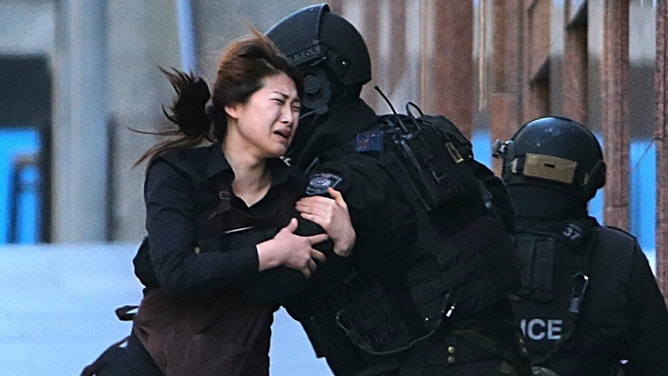 A hostage runs to armed tactical response police officers for safety after she escaped from a cafe under siege at Martin Place in the central business district of Sydney, Australia, Monday, Dec. 15, 2014. (AP / Rob Griffith)
