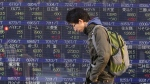 A man walks by an electronic stock board of a securities firm in Tokyo, Monday, Dec. 8, 2014. Asian stocks rallied for a second day Friday after the Federal Reserve's reassurance it was in no hurry to hike interest rates. (AP/Koji Sasahara)