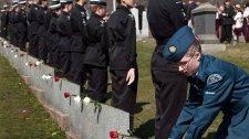 Leading Air Cadet Sharon Spears-Mandeville lays a flower on a grave marker at a memorial service at Fairview Lawn Cemetery to mark the 100th anniversary of the sinking of RMS Titanic in Halifax on Sunday, April 15, 2011. (Andrew Vaughan / THE CANADIAN PRESS)