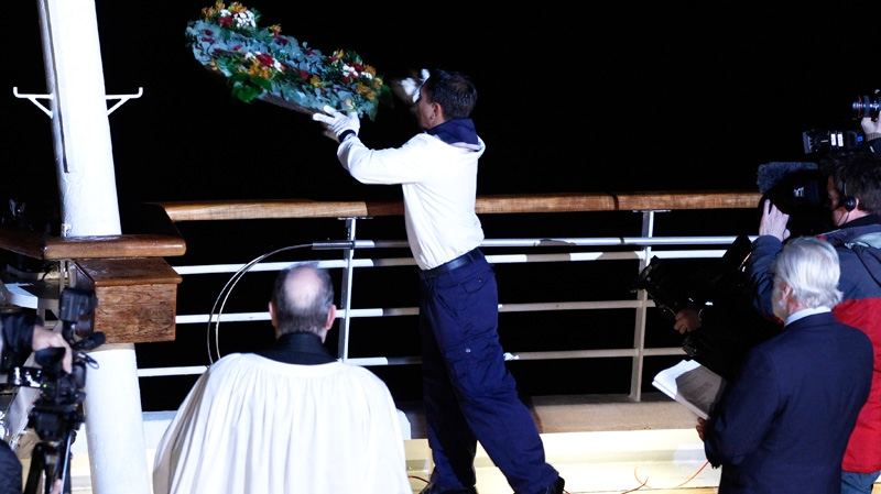 A crew member throws a wreath overboard during a memorial service, marking the 100th year anniversary of the Titanic disaster, aboard the MS Balmoral Titanic memorial cruise ship, at the wreck site in the North Atlantic Ocean, early Sunday, April 15, 2012. (AP / Lefteris Pitarakis)