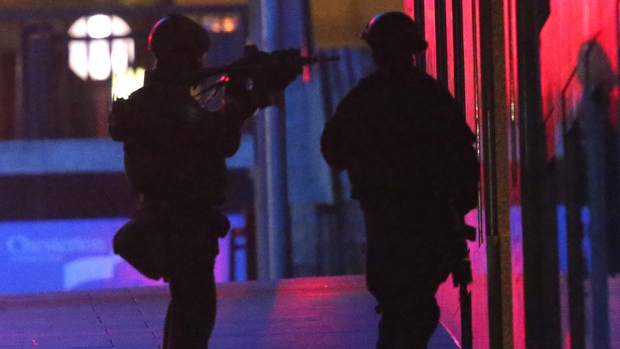 Armed tactical response officers enter the building after shots were fired during a cafe siege in the central business district of Sydney, Australia, Tuesday, Dec. 16, 2014. (AP / Rob Griffith)