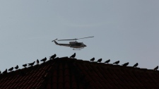 A  police helicopter flights over the old town prior to the arrival of President Barack Obama and Colombia's President Juan Manuel Santos for a land titling event for Afro-Colombian communities in Cartagena, Colombia, Sunday, April 15, 2012. (AP / Fernando Llano)