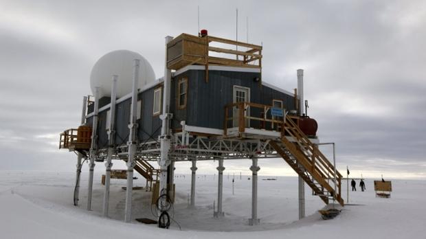 In this Friday, July 15, 2011 photo, scientists walk on the snow surrounding Summit Station, a small research facility situated 10,500 feet above sea level, on top of the Greenland ice sheet. (AP Photo/Brennan Linsley)