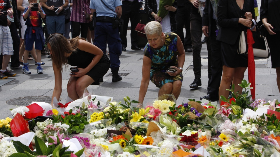 Women offer flowers at a makeshift memorial in Sydney, Australia Tuesday, Dec. 16, 2014 near where three people died in a siege. (AP / Nick Perry)