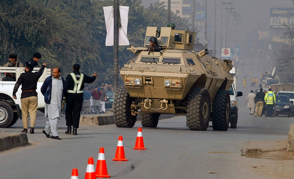 An armoured personnel carrier moves toward a school under attack by Taliban gunmen in Peshawar, Pakistan, Tuesday, Dec. 16, 2014. (AP / Mohammad Sajjad)