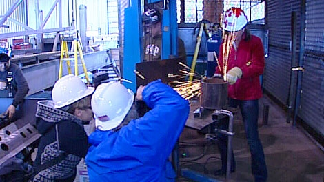 Wildrose Leader Danielle Smith (in the red jacket) rolled up her sleeves at a public appearance at an oilfield company in Nisku on Monday, April 16.